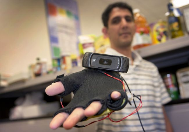 Graduate student Siddharth Advani displays the webcam-equipped haptic glove he helped design as part of the Third Eye: Visually Impaired project.